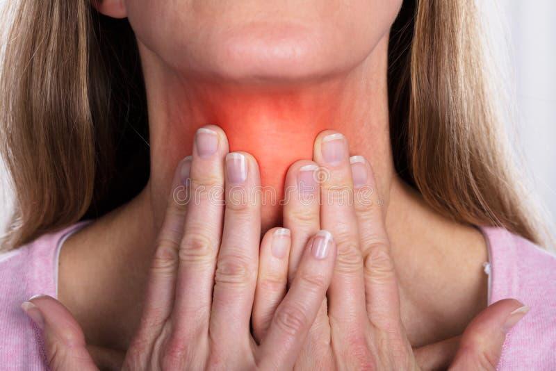 Kvinnan med halsen smärtar arkivfoto