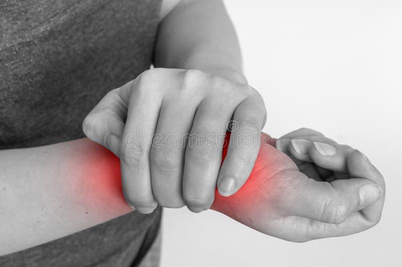 Kvinnan med handleden smärtar rymmer hennes mörbultade hand royaltyfria foton