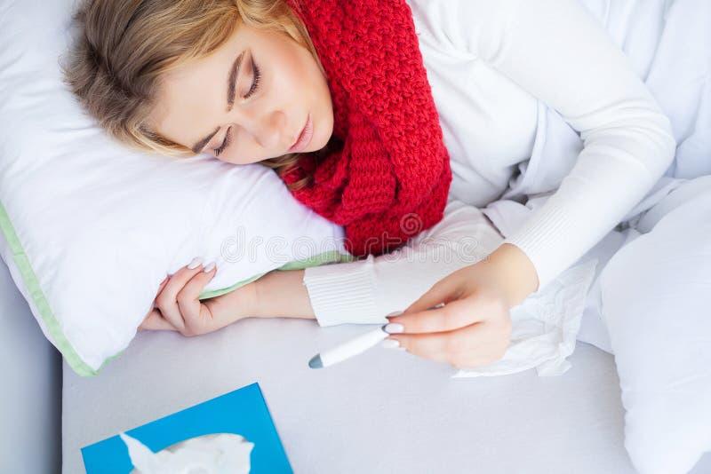 Kvinnan med influensaviruset som ligger i säng, mäter hon hennes temperatur med en termometer royaltyfri bild