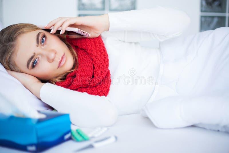 Kvinnan med influensaviruset som ligger i säng, mäter hon hennes temperatur med en termometer royaltyfri foto