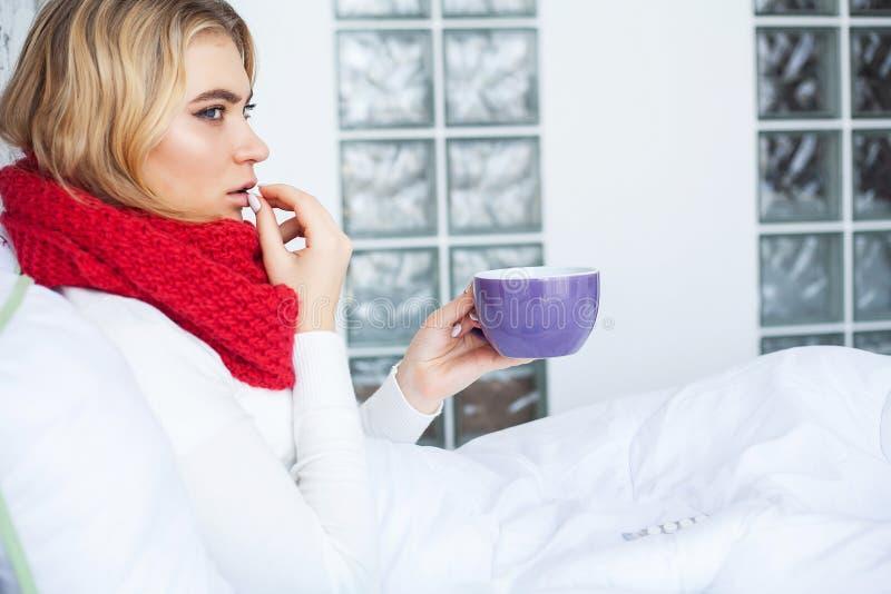 Kvinnan med influensaviruset som ligger i säng, mäter hon hennes temperatur med en termometer royaltyfri fotografi