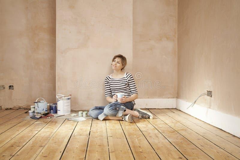 Kvinnan med kaffe rånar sammanträde på golvtilja royaltyfria foton