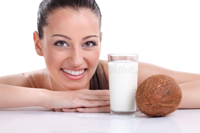 Kvinnan med kokosnöten mjölkar royaltyfri foto