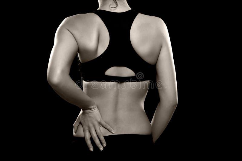 Kvinnan med lägre tillbaka smärtar arkivfoto
