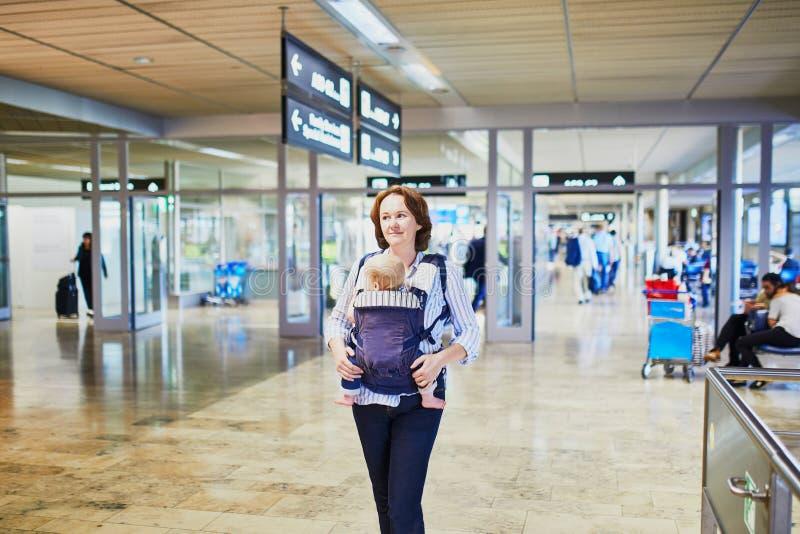 Kvinnan med lilla flickan behandla som ett barn in b?raren i internationell flygplats royaltyfri fotografi