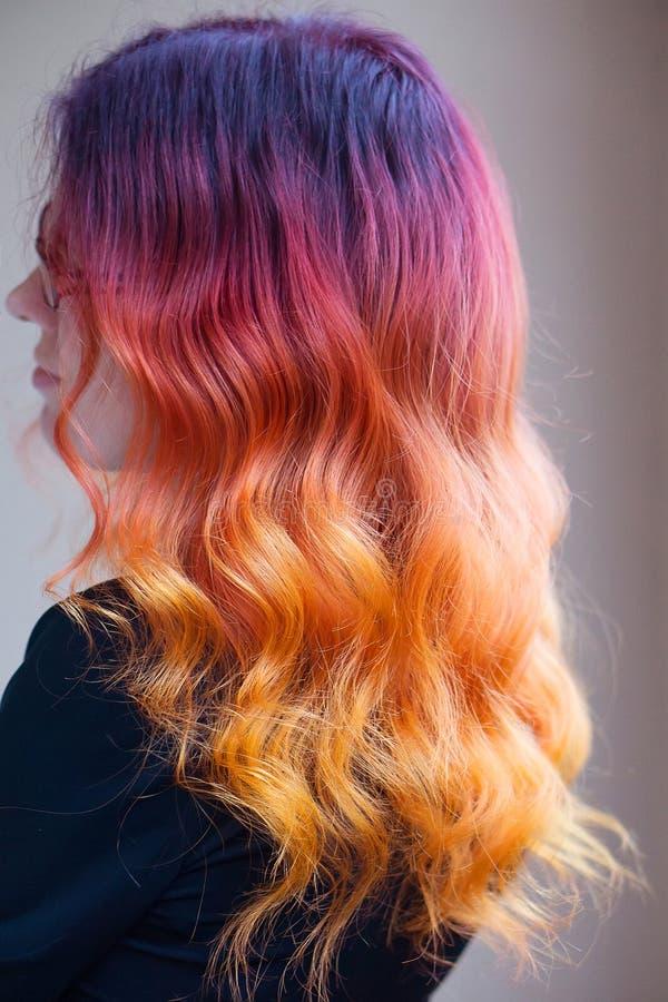 Kvinnan med ljus färglutning färgade långt lockigt hår royaltyfria foton