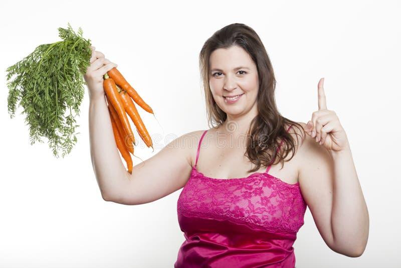 Kvinnan med morötter rymmer upp pekfingret arkivbild