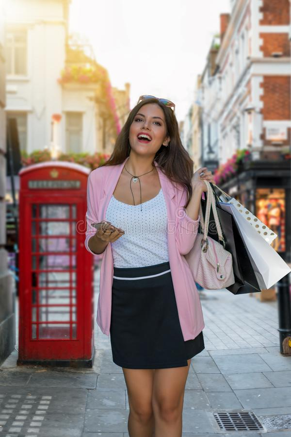 Kvinnan med påsar i hennes hand shoppar på en upptagen shoppinghighstreet i London royaltyfri foto