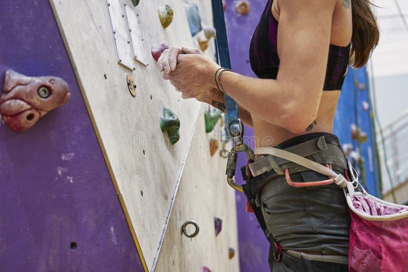 Kvinnan med perfekt passformkropputbildning på en klättringvägg i sportkorridor, ordnar till till genomköraren arkivfoto