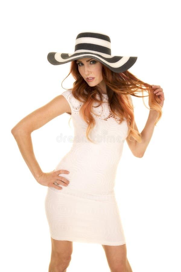 Kvinnan med rött hår i den vita klänningen och hatten spelar med hår arkivbilder