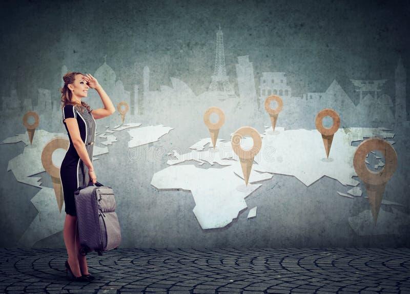 Kvinnan med resväskan som är klar att undersöka världen på gränsmärken, kartlägger bakgrund royaltyfria foton