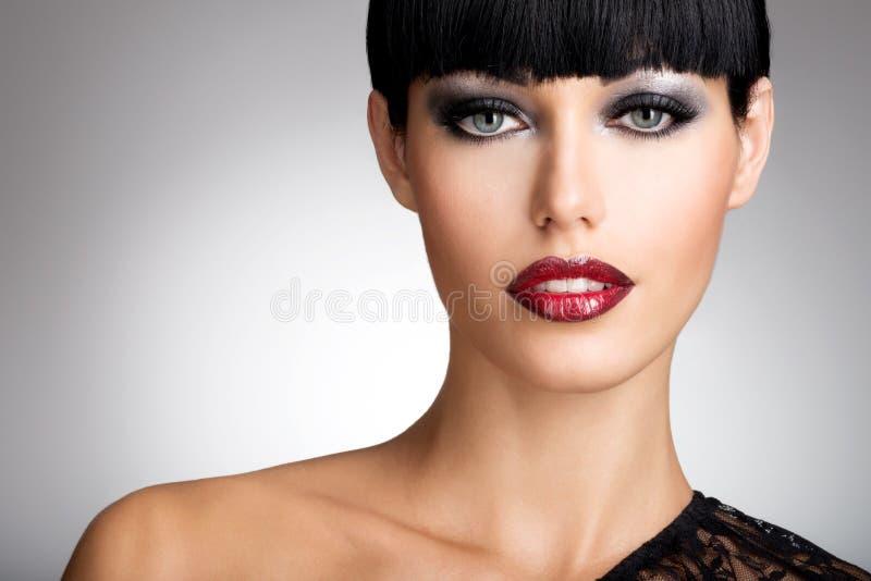 Kvinnan med sexiga röda kanter och modefärg synar makeup royaltyfria bilder