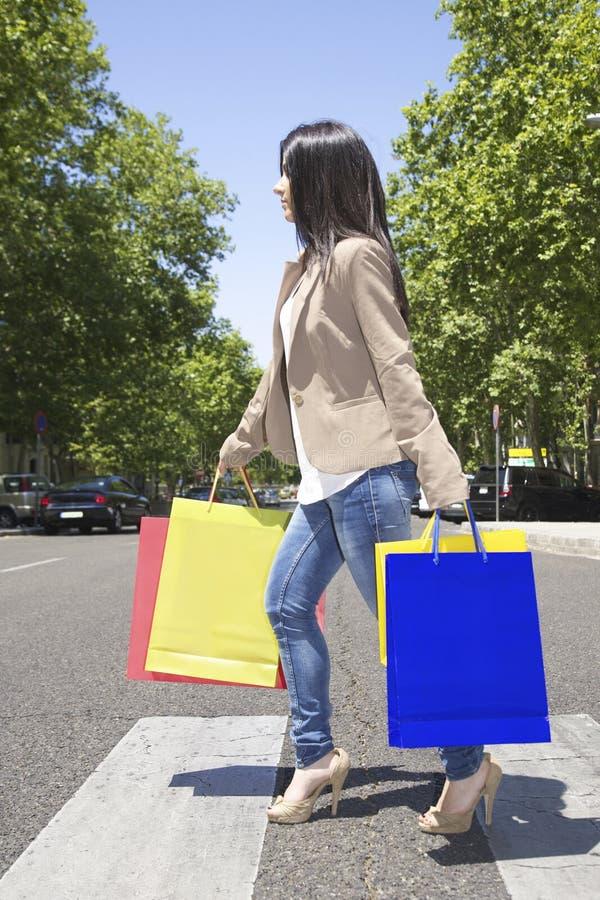 Kvinnan med shoppar påsar på övergångsställe arkivbild
