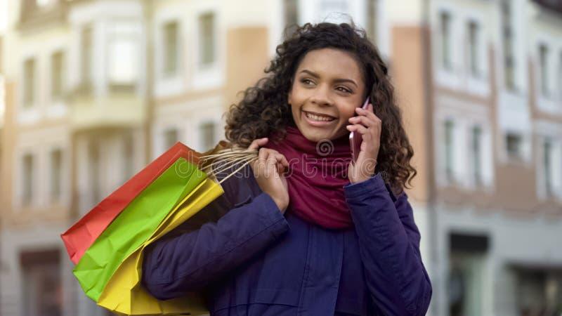 Kvinnan med shoppingpåsar som kallar kvinnliga vänner för att berätta om rabatter shoppar in arkivbilder