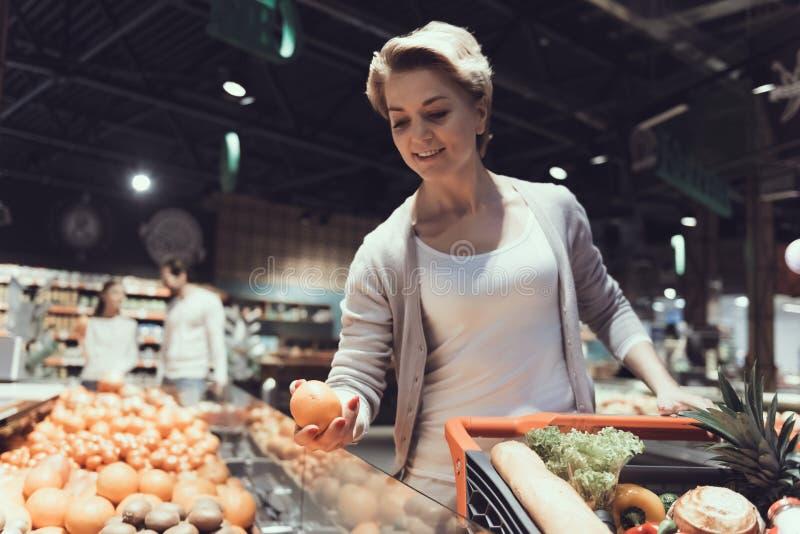 Kvinnan med shoppingvagnen som väljer frukter shoppar in arkivfoto