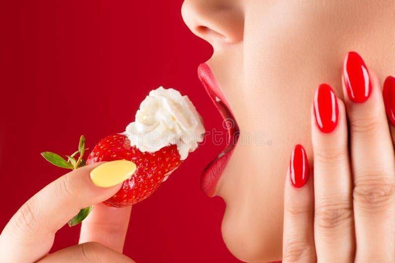 Kvinnan med sinnliga kanter äter jordgubbar med kräm royaltyfri fotografi