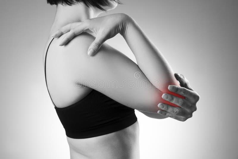 Kvinnan med smärtar i armbåge Smärta i människokroppen arkivbild