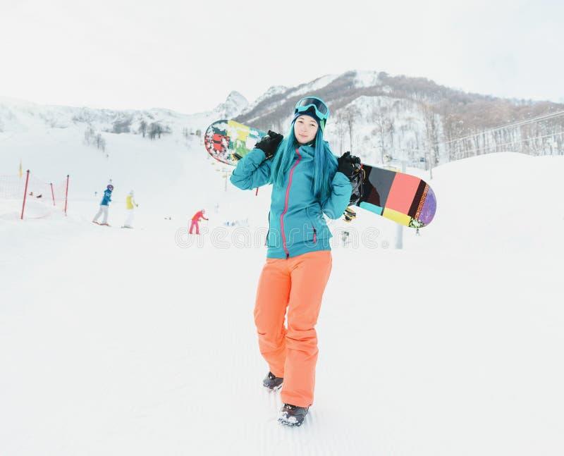 Kvinnan med snowboarden skidar på semesterorten fotografering för bildbyråer