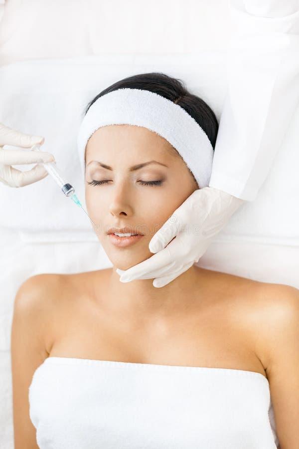 Kvinnan med stängda ögon får injektioner på framsida arkivbild