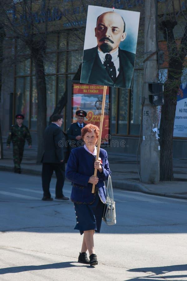 Kvinnan med ståenden av de sovjetiska grundareVladimir Lenin tagandeen särar i demonstrationen för den Maj dagen i Volgograd royaltyfri bild