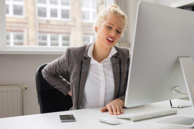 Kvinnan med tillbaka smärtar sammanträde vid datoren på kontoret arkivfoton