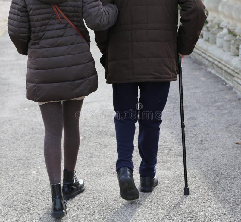 Kvinnan medföljer den äldre gentlemannen med att gå pinnen royaltyfri foto