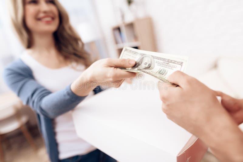 Kvinnan mottog jordlotten från leveransarbetaren Kvinnan betalar delivereren royaltyfri bild