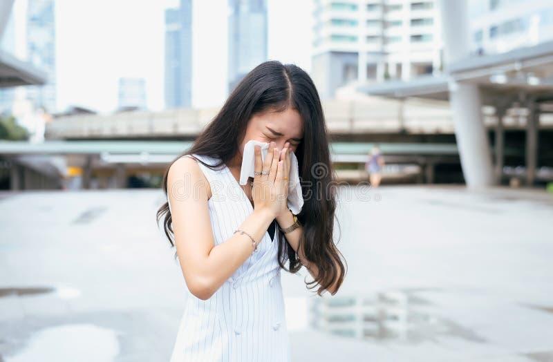Kvinnan nyser på gatan därför att förorening, den unga kvinnlign som fås näsallergi royaltyfria foton