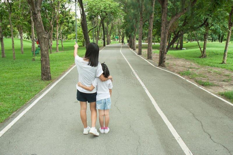 Kvinnan och barnet som går på vandringsledet och gångbanan i det offentligt, parkerar och kännande lycka och tycker om arkivbild
