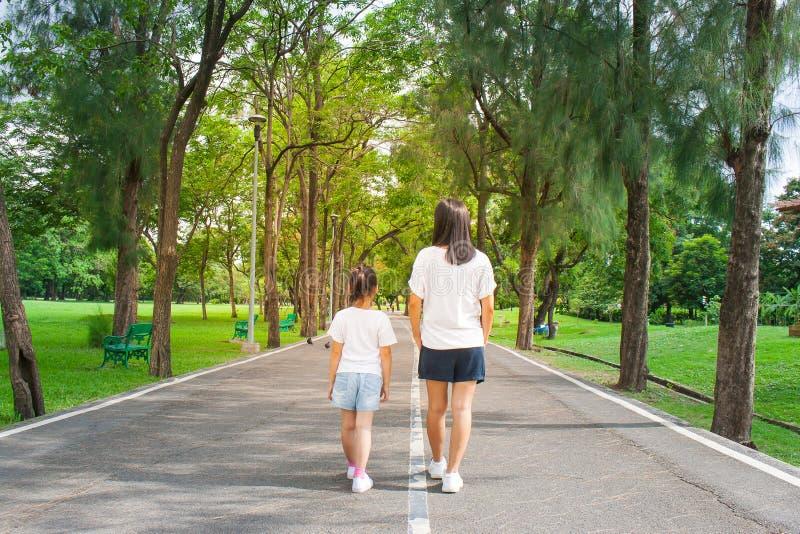 Kvinnan och barnet som går på vandringsledet och gångbanan i det offentligt, parkerar och kännande lycka och tycker om arkivfoto