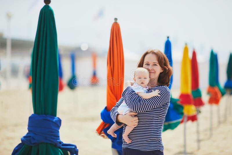 Kvinnan och behandla som ett barn lite flickan på stranden arkivfoton