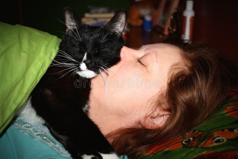 Kvinnan och den svartvita katten kurade sovande nästan fotografering för bildbyråer