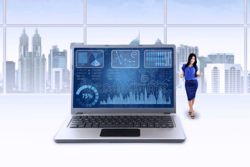 Kvinnan och diagrammet på bärbara datorn firar hennes prestation arkivbild
