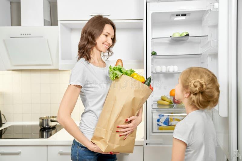 Kvinnan och dottern med produkter hänger löst nära den tomma kylen arkivbilder
