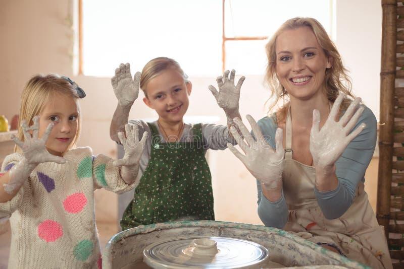 Kvinnan och flickor som visar händer i krukmakeri, shoppar royaltyfri fotografi