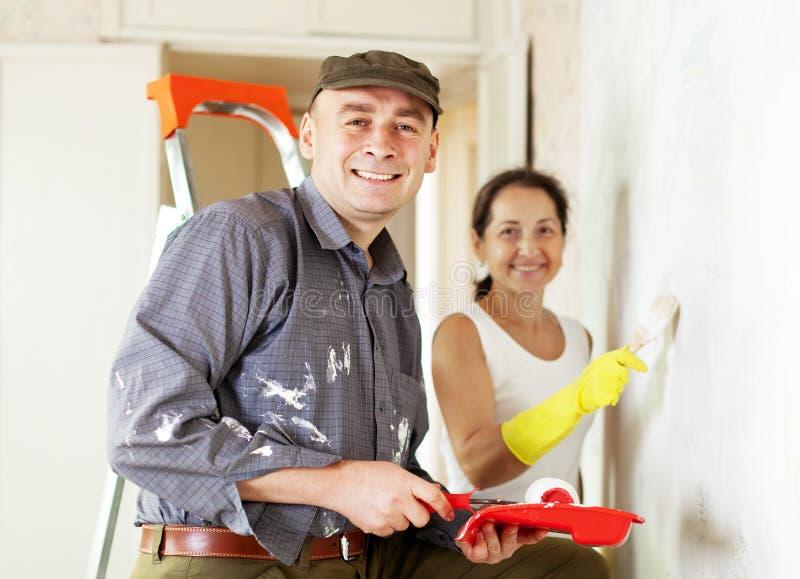Kvinnan och mannen gör reparationer i hem royaltyfria bilder