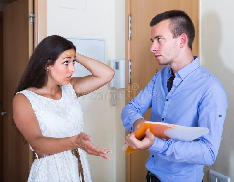 Kvinnan och mannen som den har, argumenterar med dokument på dörröppningen fotografering för bildbyråer