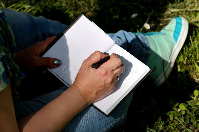 Kvinnan och studenten som sitter på gräs, tar anmärkningar i anteckningsbok och att lära och skriver tankar, skriver boken fotografering för bildbyråer