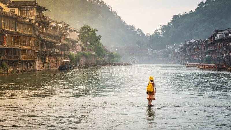 Kvinnan på att fukta stenbron över den Tuo Juang floden verkar gå på vatten i Fenghuang den forntida staden Hunan Kina royaltyfri bild