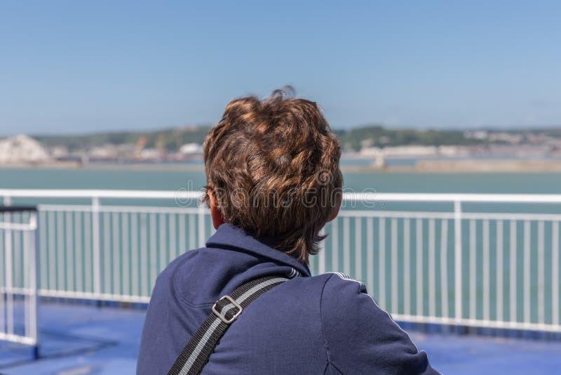 Kvinnan på färjan som lämnar Dover att se tillbaka till engelska, seglar utmed kusten royaltyfria bilder