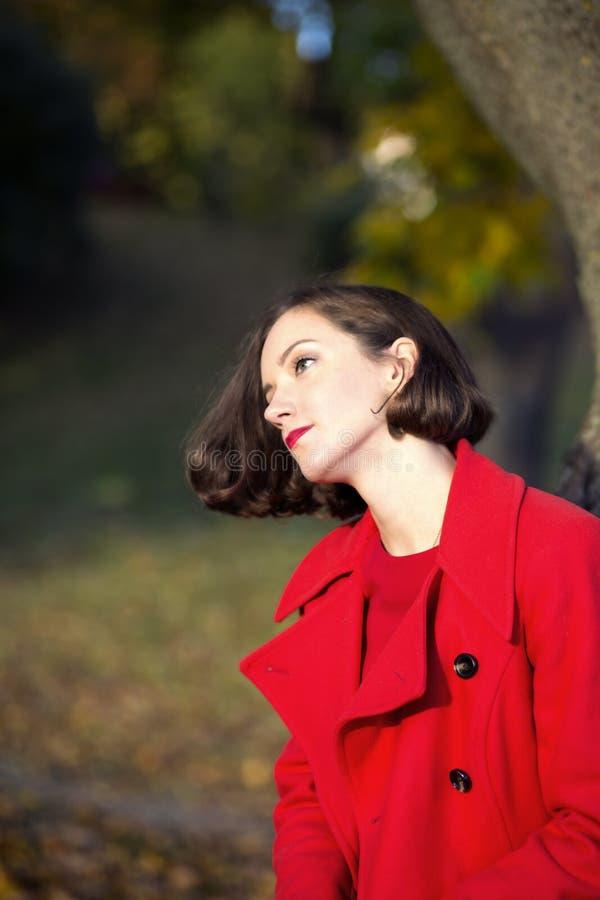 Kvinnan på hösten parkerar tycker om solig dag royaltyfria bilder