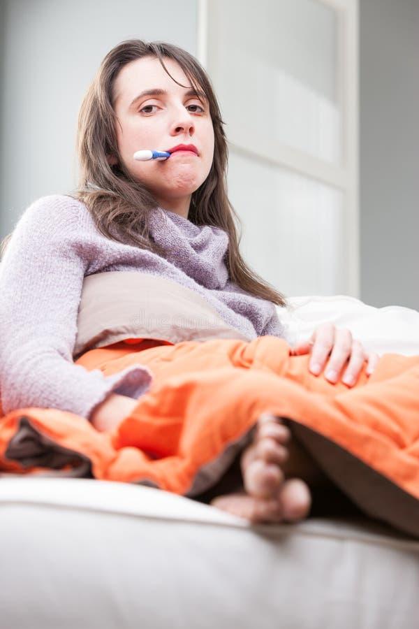 Kvinnan på hennes soffa har influensan arkivbild