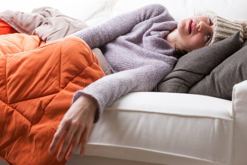 Kvinnan på hennes soffa har influensan royaltyfri bild