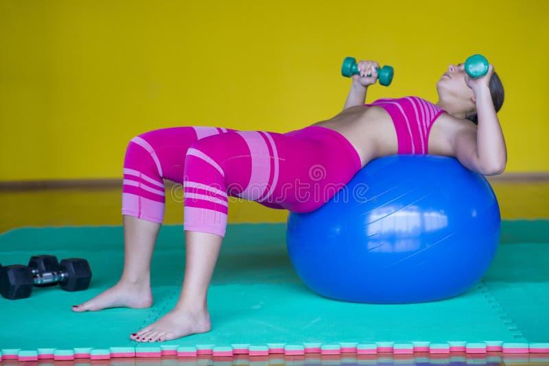Kvinnan på idrottshallen med pilates klumpa ihop sig arkivbild