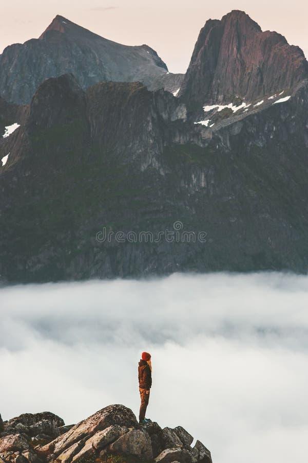 Kvinnan på klippkanten över moln reser i berg fotografering för bildbyråer