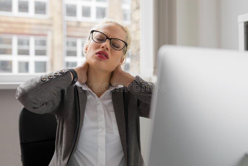Kvinnan på kontoret som har halsen, smärtar arkivbild