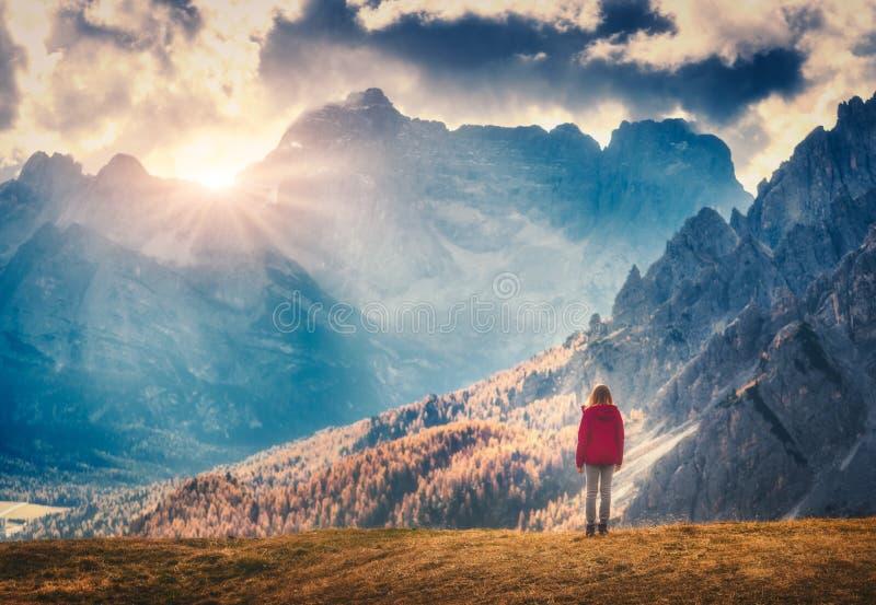Kvinnan på kullen ser på de majestätiska bergen på solnedgången royaltyfria bilder