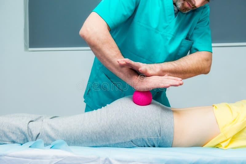 Kvinnan på massagen för sjukgymnastikhäleribollen från kiropraktor för terapeut A behandlar den tålmodiga lårbenbakdelen för ` s  royaltyfria foton