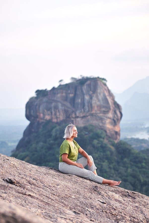 Kvinnan på Pidurangala vaggar med sikt på Sigiriya arkivfoto