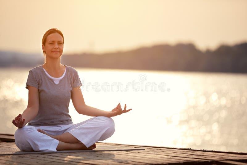 Kvinnan på skeppsdockasammanträde i yoga poserar royaltyfria foton